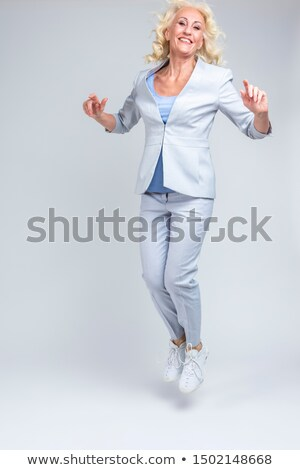 Vertical image of elderly woman moving  in studio Stock photo © deandrobot