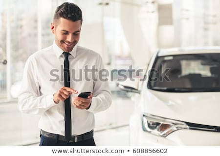 handsome man standing near car in car dealership stock photo © deandrobot