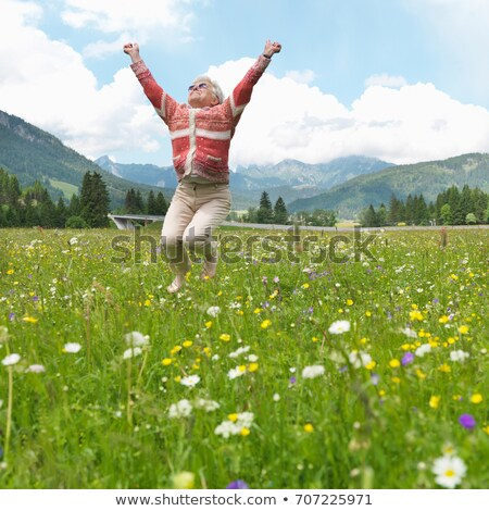 Senior woman leaping in field of flowers Stock photo © IS2