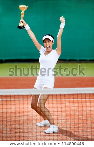 portrait of happy fitness woman holding winning sports cup stock photo © feedough