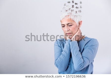Senior woman losing parts of head feeling confused as symbol of decreased mind function. Stock photo © ichiosea