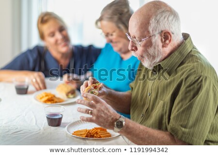 female doctor or nurse serving senior adult couple sandwiches at stock photo © feverpitch