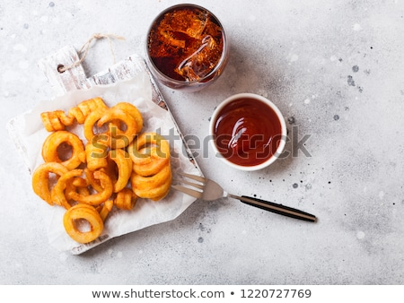 Curly fries fast food snack on wooden board with ketchup and glass of cola on stone kitchen backgrou Stock photo © DenisMArt