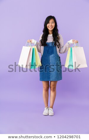 Emotional young asian beautiful attractive woman posing isolated indoors holding shopping bags. Stock photo © deandrobot