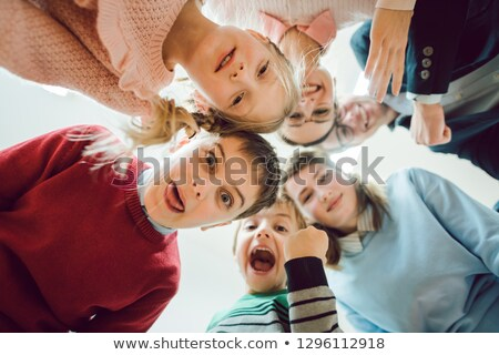funny students and teacher as a team in class room of school stock photo © kzenon