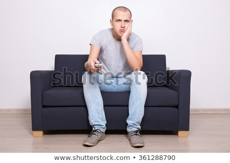 Portrait of a bored young man holding TV remote control Stock photo © deandrobot
