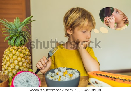 Boy eats fruit but dreams about hamburger. Harmful and healthy food for children. Child eating healt Stock photo © galitskaya