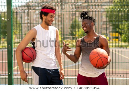 Two young friendly basketball playmates discussing some curious moments of game Stock photo © pressmaster