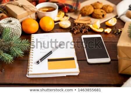 smartphone notepad page with gift list pen and credit card among festive stuff stock photo © pressmaster