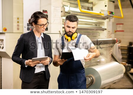 Two factory workers reading document with description of new technical equipment Stock photo © pressmaster