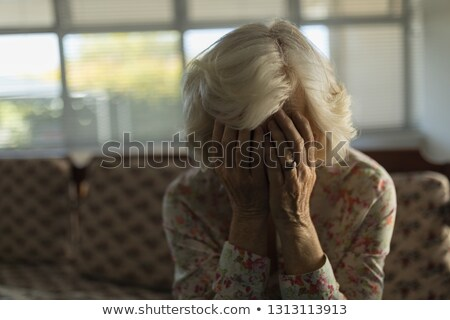 Stock photo: Front view of worried senior woman relaxing on sofa in living room at nursing home