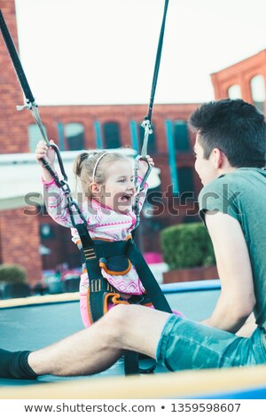 Adorable smiling girl jumping on trampoline, having fun with her Stock photo © przemekklos