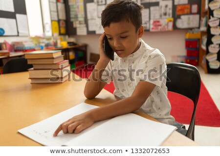 Stock photo: Front view of cute mixed-race schoolboy talking on mobile phone while studying at desk in a classroo