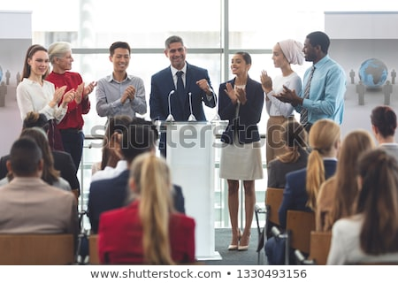 Front view of diverse group of business professionals standing on podium while speaking in front of  Stock photo © wavebreak_media