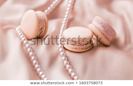Sweet macaroons and pearls jewellery on silk background, parisia Stock photo © Anneleven