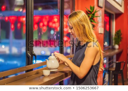 A young woman drinks Chinese tea on a background of red Chinese lanterns in honor of the Chinese New Stock photo © galitskaya