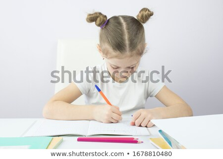 Concentrated young girl writing notes in notebook. Stock photo © deandrobot