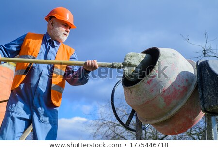 Labourer shovelling gravel into a mixer Stock photo © photography33