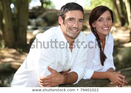 Couple in white leaning on a wooden fence Stock photo © photography33