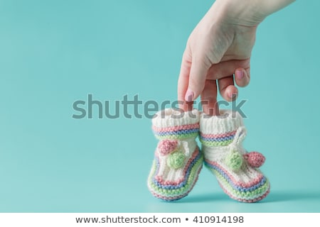 Young pregnant woman holding small baby shoes Stock photo © dash