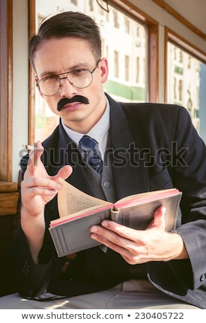 man in suit with glasses and whiskers reading book in the old to stock photo © feelphotoart