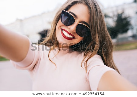 Closeup portrait of a smiling fashionable woman Stock photo © deandrobot