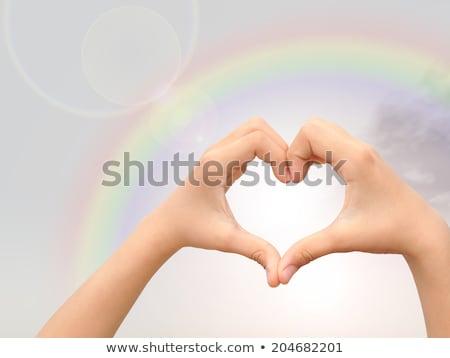 Insan eller gökkuşağı kalp şekli mavi gökyüzü insanlar Stok fotoğraf © dolgachov