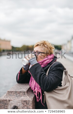 trendy woman drinking takeaway coffee and walking on the waterfr stock photo © vlad_star