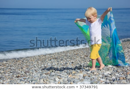 child with shawl goes on pebble beach Stock photo © Paha_L