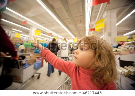Small girl sit in shoppingcart in supermarket and show by finger Stock photo © Paha_L