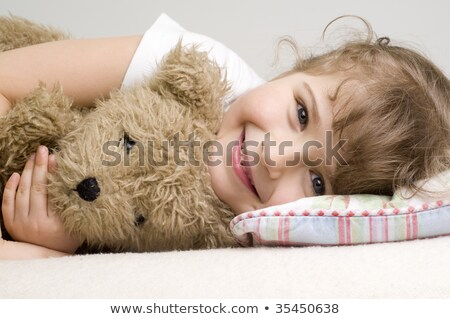 Woman lying on the bed with teddy bear Stock photo © deandrobot