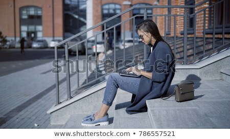 side view of woman using laptop on stairs stock photo © dash