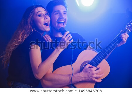 smiling handsome young man with guitar singing in microphone stock photo © deandrobot