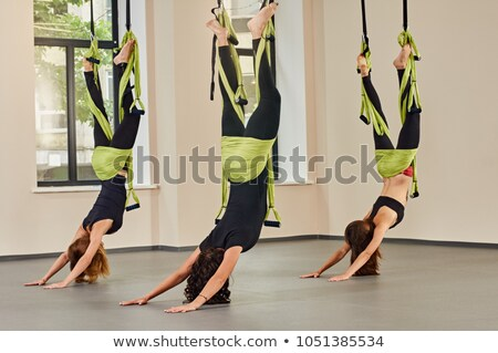 Legs of sportswoman doing aerial yoga exercise Stock photo © deandrobot