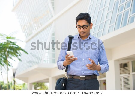 Smiling young businessman drinking coffee and using cell phone outdoors Stock photo © deandrobot