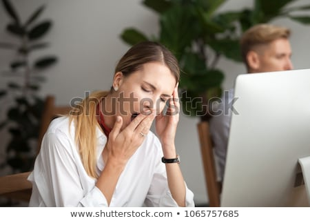 Tired businesswoman working overtime and yawning in office Stock photo © stevanovicigor
