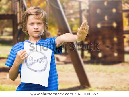 Sad boy holdingn anti bullying sign  against playground Stock photo © wavebreak_media