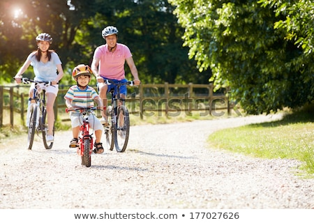 Active Asian children riding bicycle outdoor. Stock photo © szefei