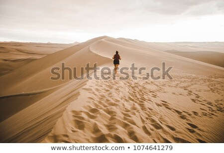 woman walking across desert sand dunes stock photo © monkey_business