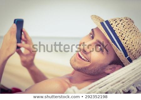 Сток-фото: человека · расслабляющая · гамак · говорить · мобильного · телефона · пляж