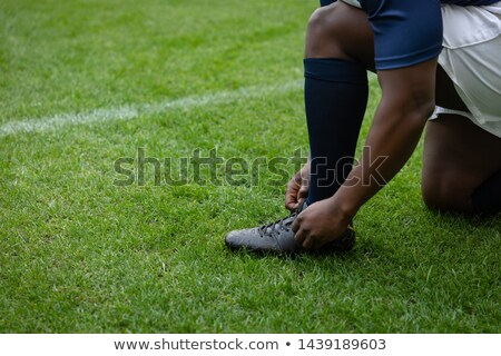 Low section of rugby player tying shoes Stock photo © wavebreak_media