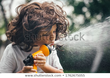 Boy with water hose Stock photo © IS2