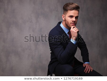 pensive businessman in navy suit sitting on wooden stool stock photo © feedough