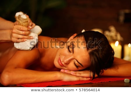 therapist giving massage with herbal compress balls to woman stock photo © andreypopov