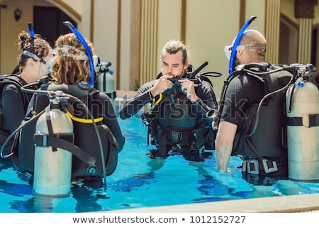 Diving instructor and students. Instructor teaches students to dive Stock photo © galitskaya