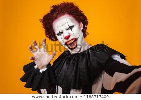 Shocked clown man 20s wearing black costume and halloween makeup Stock photo © deandrobot