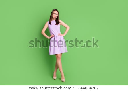Stylish brunette in beige dress with hand on waist. stock photo © studiolucky