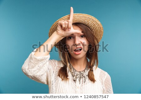 Cute pretty woman showing funny gesture grimace isolated over blue wall background. Stock photo © deandrobot