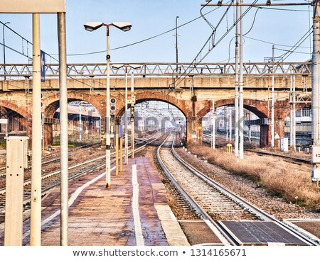 railway with catenaries crossing a bricks bridge in an european stock photo © photooiasson