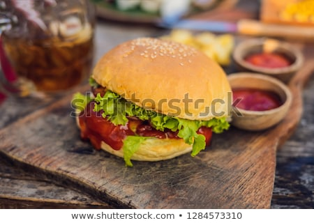 Closeup of fresh burger with French fries on wooden table with bowls of tomato sauce. lifestyle food Stock photo © galitskaya